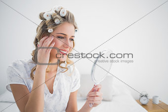 Happy blonde with hair curlers looking at reflection