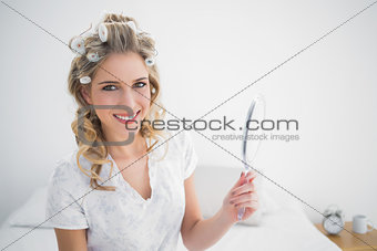 Smiling blonde wearing hair curlers