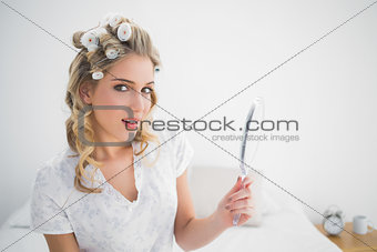 Cheerful gorgeous blonde wearing hair curlers