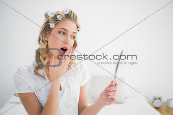 Pretty blonde wearing hair curlers yawning