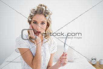 Surprised gorgeous blonde wearing hair curlers posing
