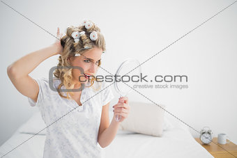 Cheerful gorgeous blonde wearing hair curlers posing