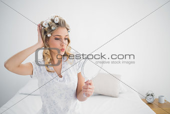 Gorgeous blonde wearing hair curlers kissing while looking at her reflection