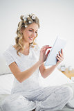 Happy blonde wearing hair curlers using tablet