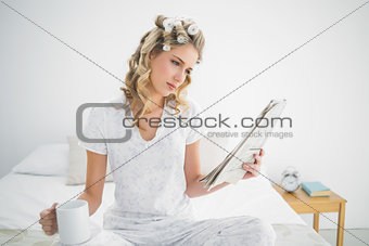 Focused cute blonde wearing hair curlers reading newspaper
