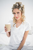 Peaceful pretty blonde wearing hair curlers holding coffee