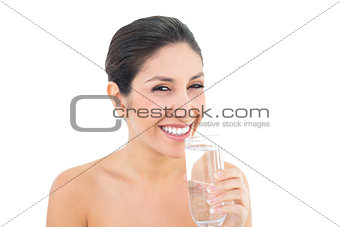 Smiling brunette holding glass of water and looking at camera