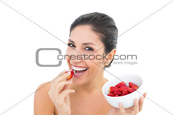 Attractive brunette holding a bowl of fresh strawberries and eating one
