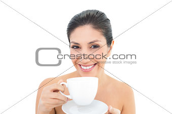Attractive brunette holding a cup and saucer and smiling at camera