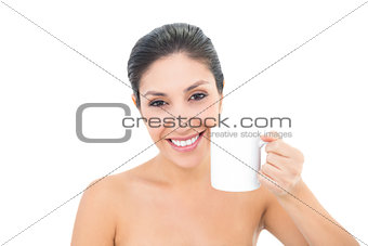 Attractive brunette holding a white mug and smiling at camera