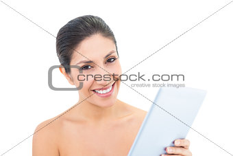 Attractive brunette using a digital tablet and smiling at camera