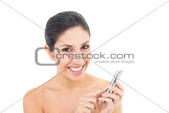 Attractive brunette using a smartphone and smiling at camera