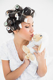 Brunette in hair rollers kissing sheep teddy