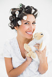 Happy brunette in hair rollers holding sheep teddy