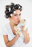 Happy brunette in hair rollers kissing sheep teddy