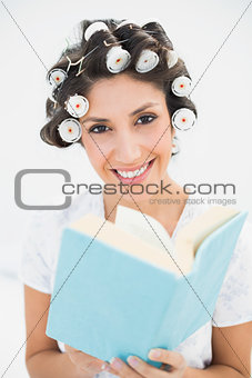 Smiling brunette in hair rollers holding a book on bed