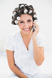 Pretty brunette in hair rollers on the phone on bed