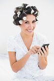 Pretty brunette in hair rollers using smartphone on bed looking at camera