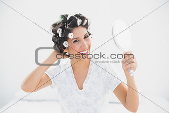 Smiling brunette in hair rollers holding hand mirror