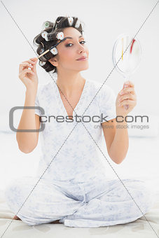 Happy brunette in hair rollers holding hand mirror and brushing her eyebrows