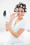 Pretty brunette in hair rollers holding hand mirror and using eyelash curler