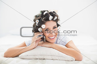 Smiling brunette in hair rollers lying on her bed making a phone call
