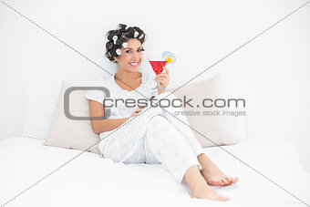 Smiling brunette in hair curlers sitting on her bed holding a cocktail