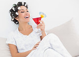 Happy brunette in hair curlers sitting on her bed holding a cocktail