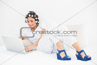 Smiling brunette in hair rollers and wedge shoes using her laptop on bed