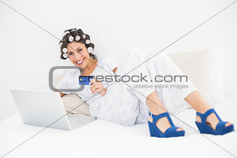 Brunette in hair rollers and wedge shoes using her laptop to shop online on bed