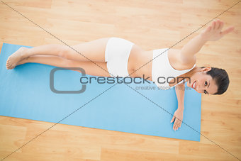 Fit woman doing a side plank and smiling at camera