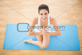 Fit woman sitting in cow face pose smiling at camera