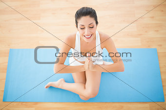 Fit woman meditating in cow face pose