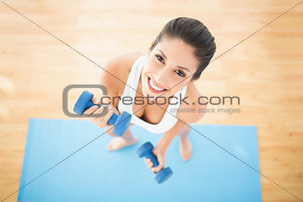 Fit woman exercising with dumbbells on blue exercise mat