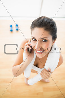 Fit woman on the phone smiling at camera