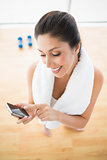 Fit woman using smartphone taking a break from workout
