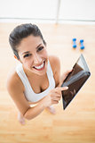 Fit woman using tablet taking a break from workout smiling at camera