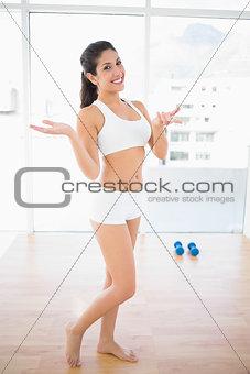 Fit confident woman smiling at camera and shrugging