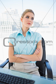 Thoughtful classy businesswoman crossing arms