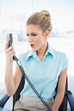 Furious stylish businesswoman shouting on the phone