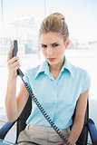 Frowning stylish businesswoman holding the phone