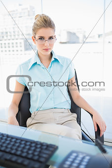 Serious businesswoman wearing glasses posing