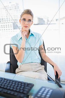 Thoughtful businesswoman wearing glasses posing