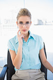 Pensive businesswoman wearing glasses posing