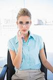 Pensive businesswoman wearing glasses posing