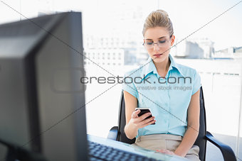Focused businesswoman wearing glasses text messaging