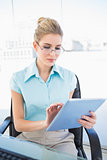 Focused businesswoman wearing glasses using tablet