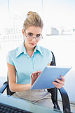 Serious businesswoman wearing glasses using tablet