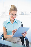 Smiling businesswoman wearing glasses using tablet