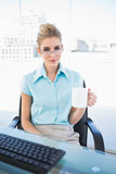 Serious businesswoman wearing glasses holding coffee